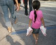 little girl carrying her brother's sneakers